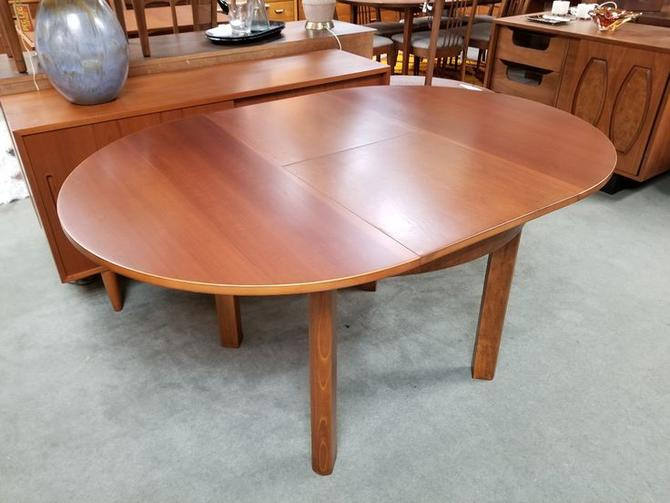 Mid-Century Modern round makore wood dining table with butterfly leaf