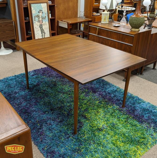 Walnut boatshape dining table from the Perspecta collection by Kent Koffey