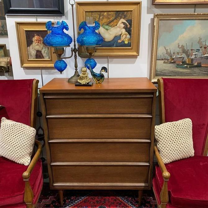 4 drawer Basset dresser flanked by stoic deep red velvet chairs
