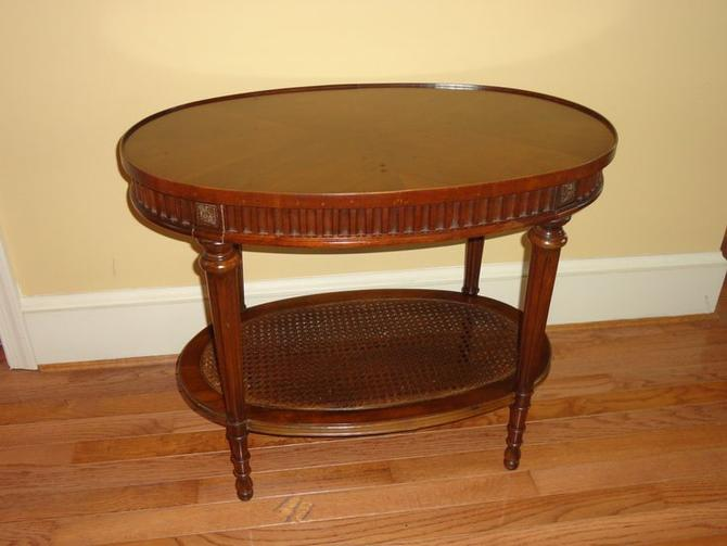 Beautiful oval side table with a rattan bottom.  Makes a perfect surface for drinks in a bar area, next to a reading chair or a bed.
