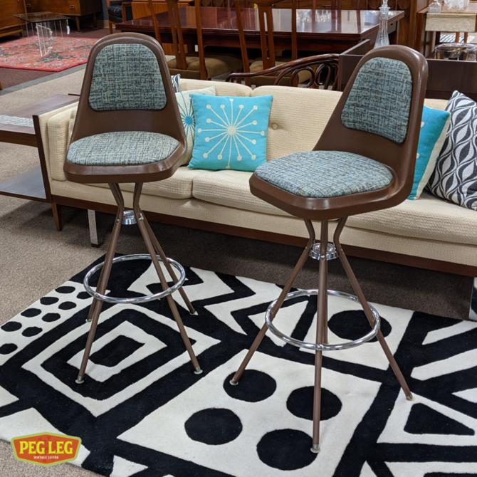 Pair of Mid-Century Modern bar stools with molded plastic seats and new upholstery