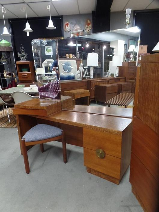 Mid-Century Modern burlwood vanity with large brass pulls and bi-fold mirror