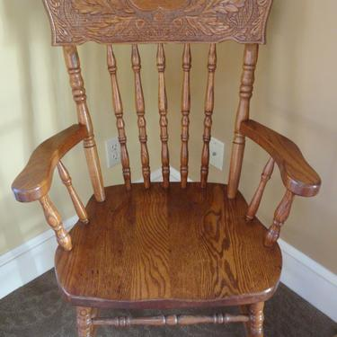 Captain's chair.  Made out of oak.  Has beautiful carving on the back rest.  Very sturdy.  Is great for extra seating in the living room or can