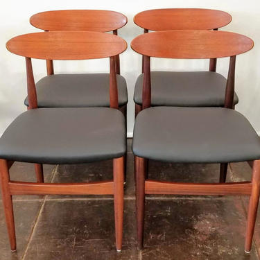 Set of four afrormosia and teak wood dining chairs with black seats.