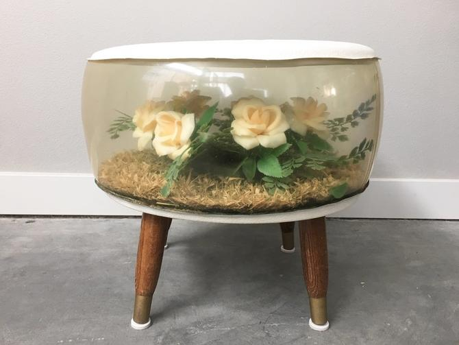 vintage mid century inflatable terrarium ottoman with floral arrangement.