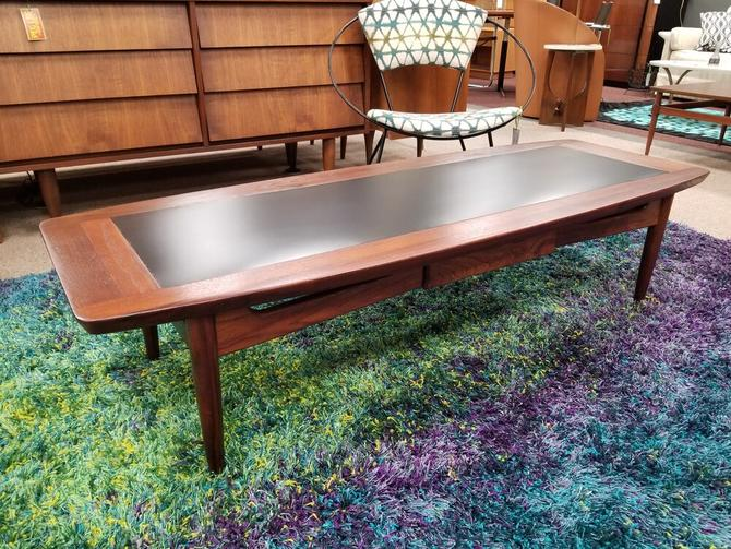 Mid-Century walnut and black surfboard coffee table with lower drawer by American of Martinsville