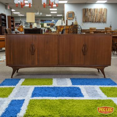 Mid-Century Modern walnut credenza with sculpted legs and pulls