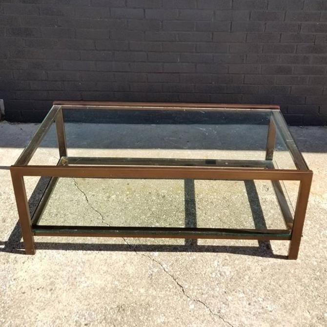 "Metal and glass two tier coffee table. (Minor scratches on glass) 44"" wide, 22"" deep, 17"" height"