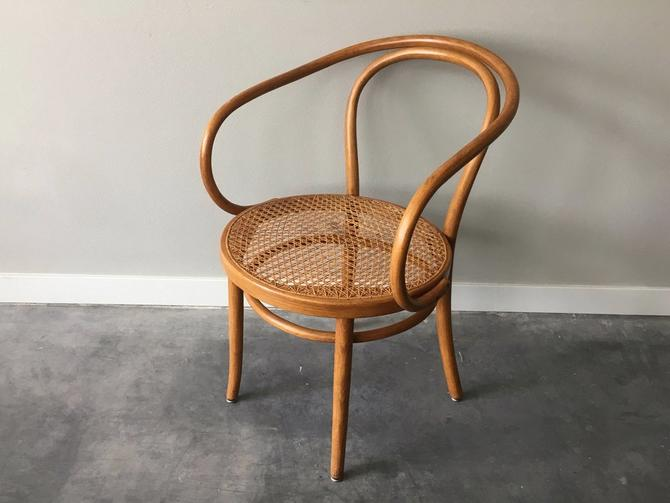 vintage mid century modern bent wood arm chair with cane seat.