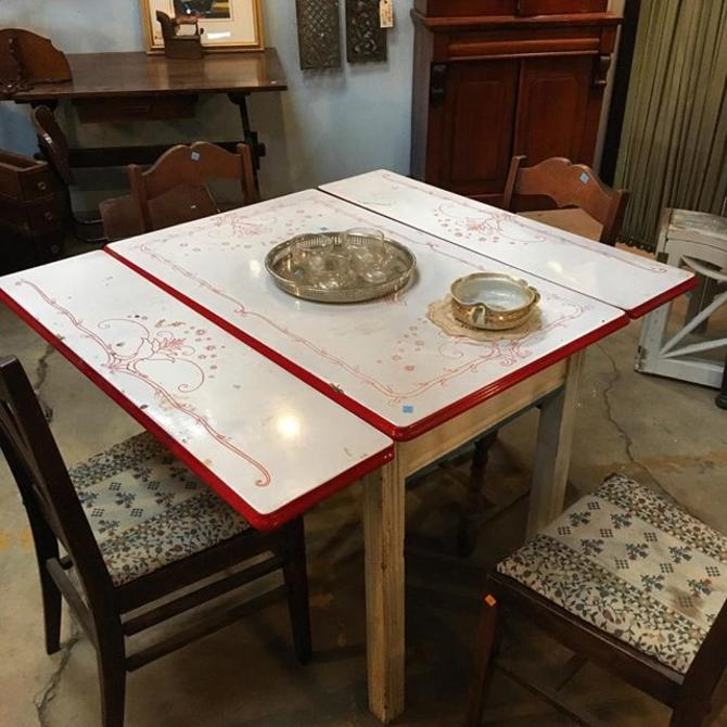Retro kitchen table. White enamel top with red details. Wood base and legs.